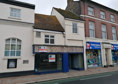 FOR SALE BY AUCTION: A Town Centre premises with upper parts and potential for development.